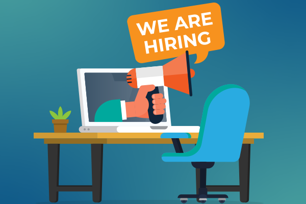 Desk and chair with hand holding megaphone with sign saying are hiring